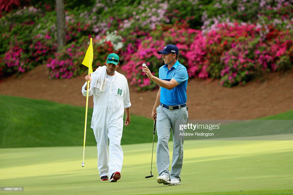 Jordan Spieth of the United States makes birdie on the 13th green as his caddie Michael Greller looks on during the first round of the 2015 Masters Tournament at Augusta National Golf Club on April 9, 2015 in Augusta, Georgia.
