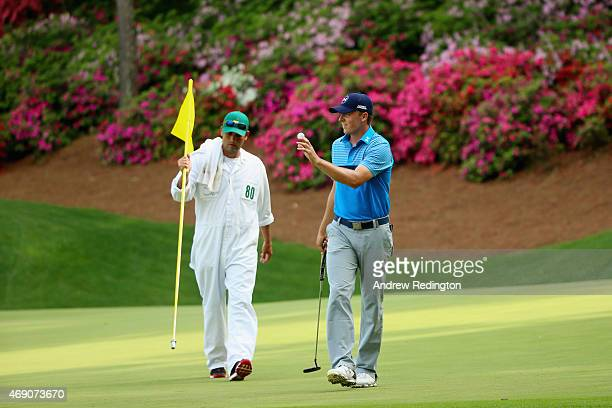 Jordan Spieth of the United States makes birdie on the 13th green as his caddie Michael Greller looks on during the first round of the 2015 Masters...