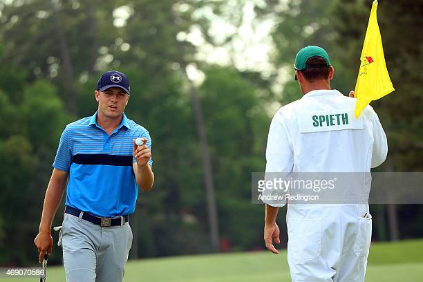 Jordan Spieth of the United States makes birdie on the 14th green as his caddie Michael Greller looks on during the first round of the 2015 Masters...