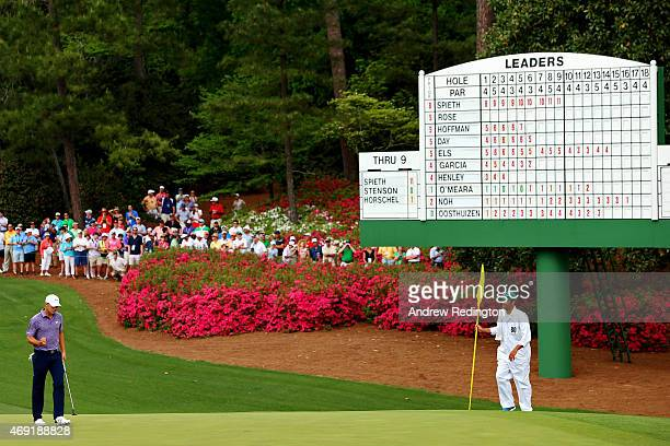 Jordan Spieth of the United States makes birdie on the tenth hole as his caddie Michael Greller looks on during the second round of the 2015 Masters...