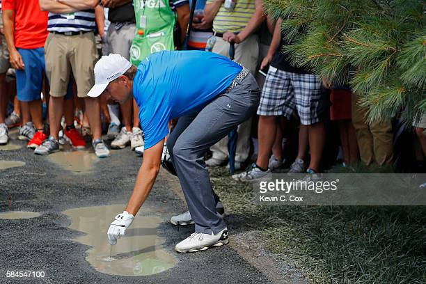 Jordan Spieth of the United States picks his ball up out of casual water after a drop ruling on the seventh hole during the second round of the 2016...