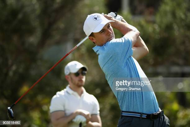 Jordan Spieth of the United States plays a shot as Nick Jonas looks on during the proam tournament prior to the Sony Open In Hawaii at Waialae...