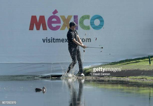 Jordan Spieth of the United States plays his second shot on the par 3, 17th hole from the waters edge during the final round of the World Golf...