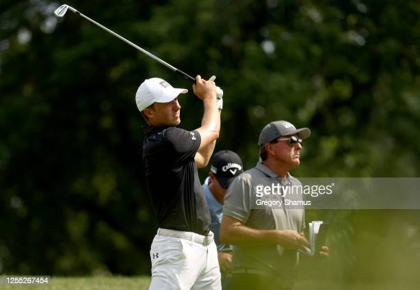 Jordan Spieth of the United States plays his shot from the 12th tee as Phil Mickelson of the United States looks on during the first round of the...