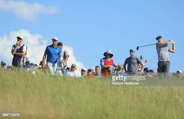 Jordan Spieth of the United States plays his shot from the tenth tee as Dustin Johnson of the United States and Martin Kaymer of Germany look on...