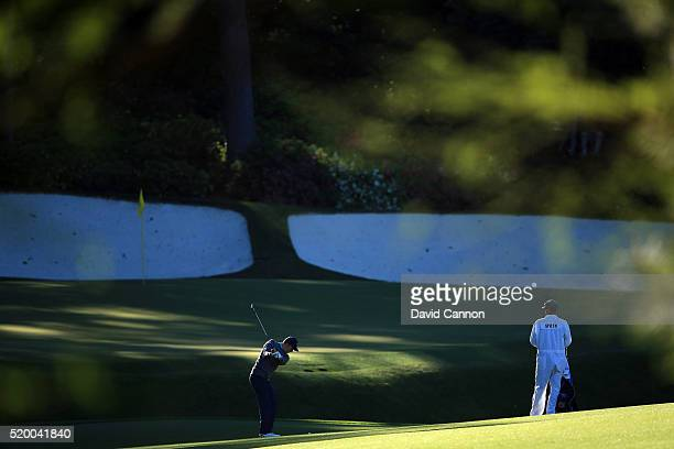 Jordan Spieth of the United States plays his third shot on the 13th hole as caddie Michael Greller looks on during the third round of the 2016...