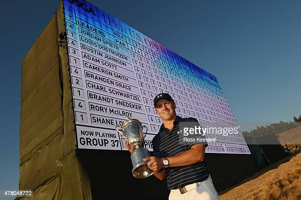 Jordan Spieth of the United States poses in front of the leaderboard with the trophy after winning the 115th U.S. Open Championship at Chambers Bay...