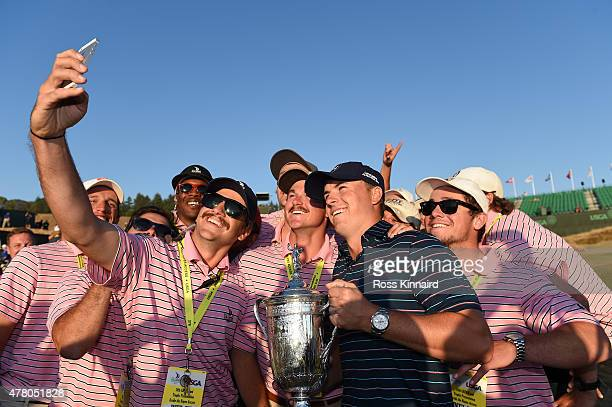 Jordan Spieth of the United States poses with the trophy amid a group of workers after winning the 115th US Open Championship at Chambers Bay on June...