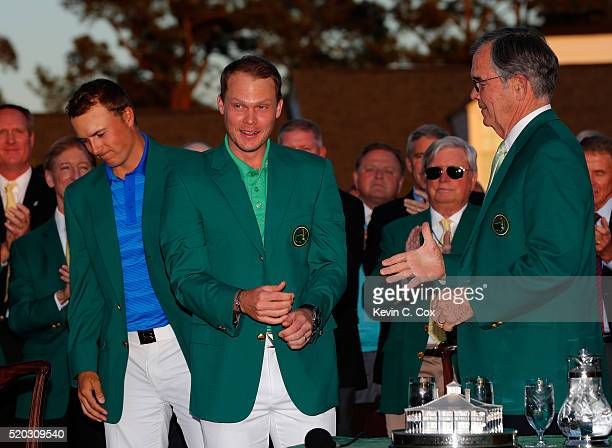 Jordan Spieth of the United States presents Danny Willett of England with the green jacket as Chairman of Augusta National William Porter Payne looks...