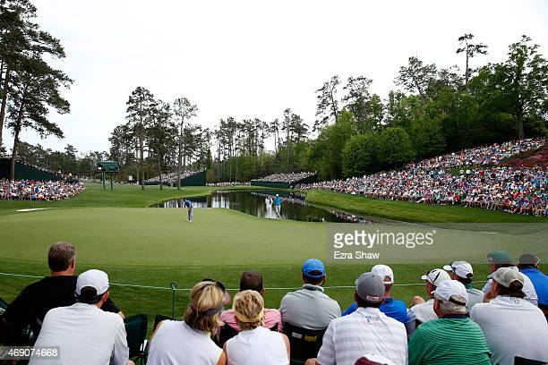 Jordan Spieth of the United States putts on the 16th green as a gallery of patrons look on during the first round of the 2015 Masters Tournament at...