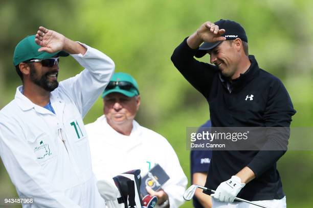 Jordan Spieth of the United States reacts on the 12th tee with caddie Michael Greller during the final round of the 2018 Masters Tournament at...