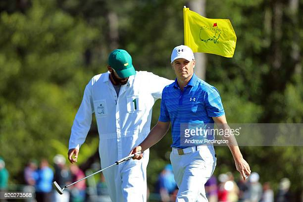 Jordan Spieth of the United States reacts to his birdie on the eighth green as caddie Michael Greller looks on during the final round of the 2016...