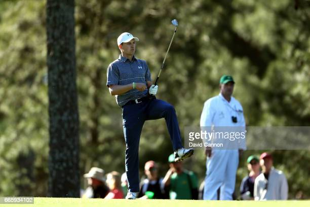 Jordan Spieth of the United States reacts to his second shot on the 14th hole as caddie Michael Greller looks on during the second round of the 2017...