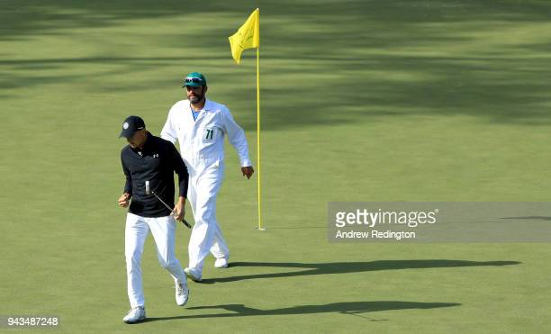 Jordan Spieth of the United States reacts to making birdie on the 15th green alongside caddie Michael Greller during the final round of the 2018...
