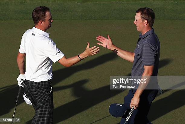 Jordan Spieth of the United States shakes hands with Justin Thomas of the United States on the 16th green after Spieth won their match 32 during the...
