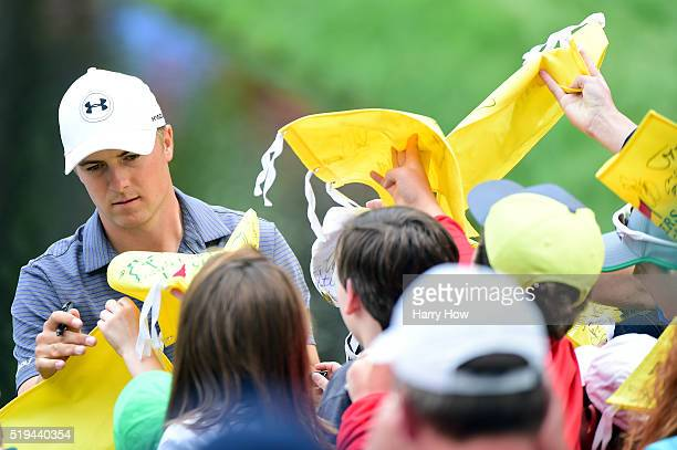 Jordan Spieth of the United States signs autographs during the Par 3 Contest prior to the start of the 2016 Masters Tournament at Augusta National...