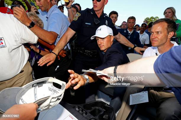 Jordan Spieth of the United States signs autographs for fans after defeating Daniel Berger in a playoff in the final round of the Travelers...