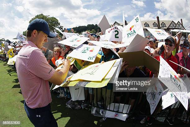 Jordan Spieth of the United States signs his autograph for fans during a practice round prior to the 2016 PGA Championship at Baltusrol Golf Club on...