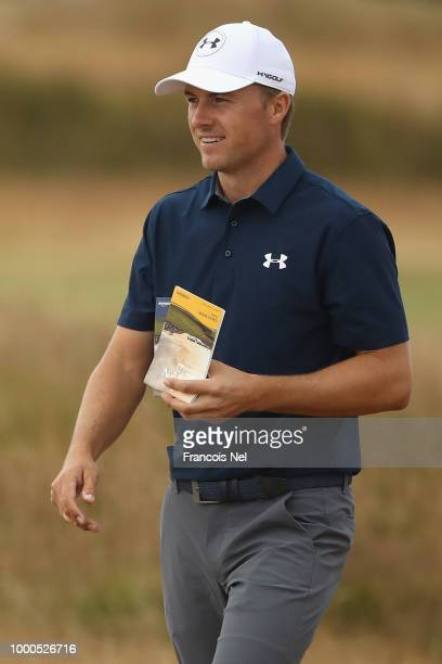 Jordan Spieth of the United States smiles with his course guide strokesaver during previews to the 147th Open Championship at Carnoustie Golf Club on...