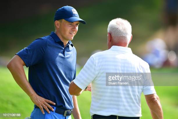 Jordan Spieth of the United States talks with Gerry McIlroy during a practice round prior to the 2018 PGA Championship at Bellerive Country Club on...