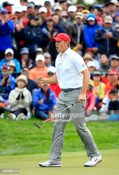 Jordan Spieth of the United States team celebrates as he holed his match winning par putt on the 18th hole in his match with Dustin Johnson against...
