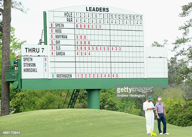 Jordan Spieth of the United States waits alongside his caddie Michael Greller in front of a leaderboard on the eighth hole during the second round of...