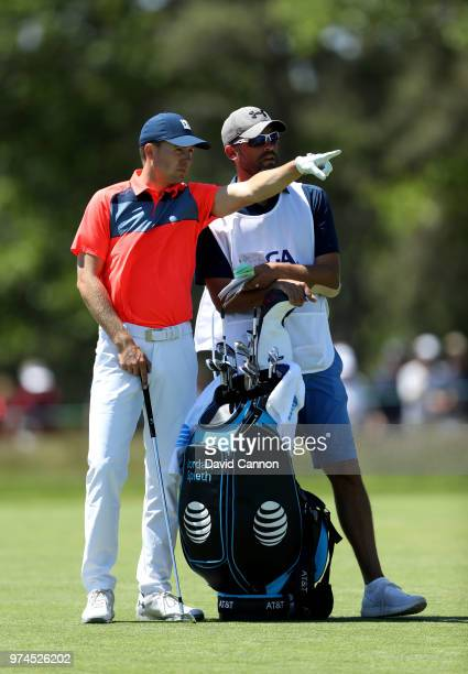 Jordan Spieth of the United States waits to play his second shot on the third hole with his caddie Michael Greller during the first round of the 2018...
