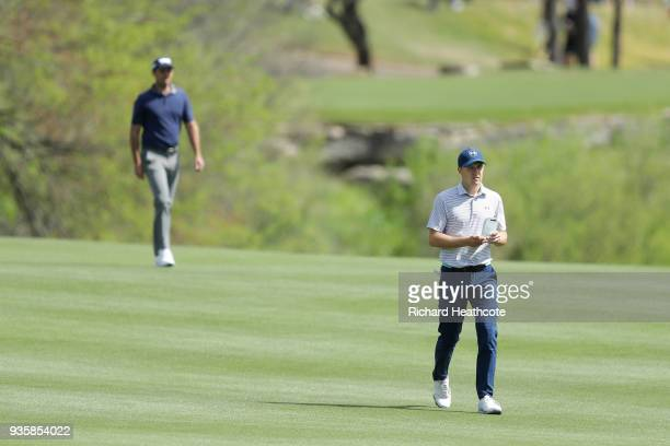 Jordan Spieth of the United States walks ahead of Charl Schwartzel of South Africa on the second hole during the first round of the World Golf...