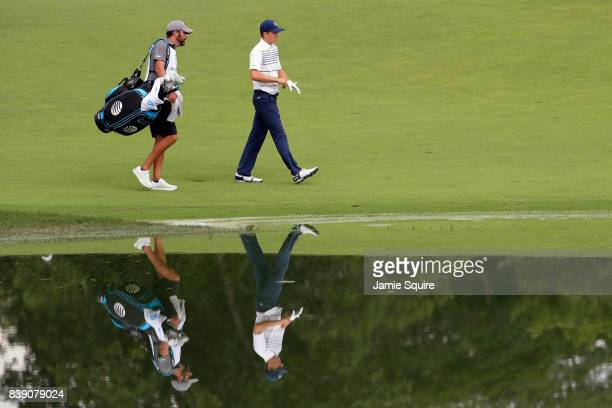 Jordan Spieth of the United States walks on the 15th hole with caddie Michael Greller during round two of The Northern Trust at Glen Oaks Club on...