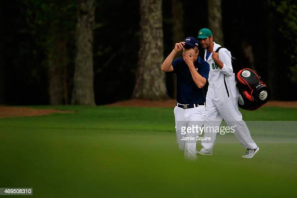 Jordan Spieth of the United States walks up the 18th fairway alongside his caddie Michael Greller during the final round of the 2015 Masters...