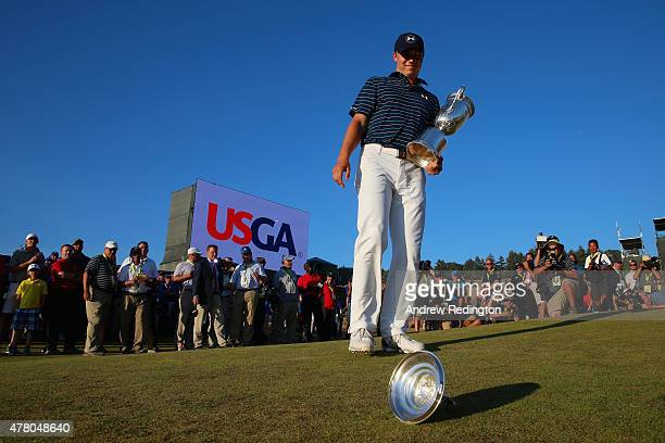 Jordan Spieth of the United States watches as the top of the trophy falls off after winning the 115th US Open Championship at Chambers Bay on June 21...