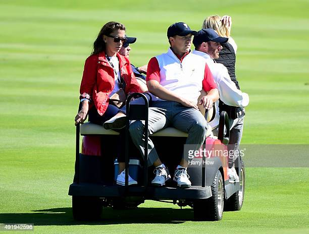 Jordan Spieth of the Unted States Team rides off on a golf cart with girlfriend Annie Verret as Davis Love III and Dustin Johnson look on after...