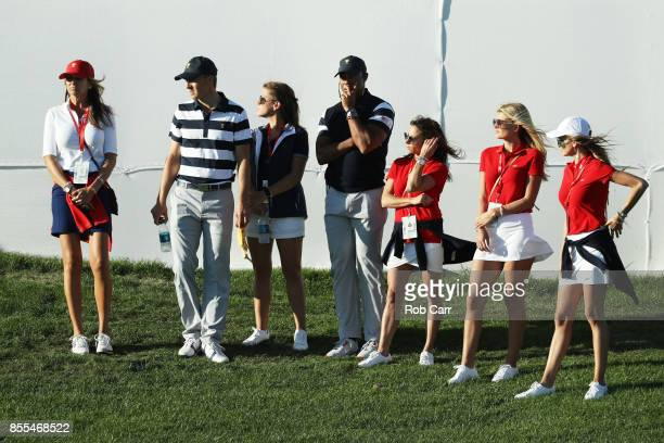 Jordan Spieth of the US Team and Captain's assistant Tiger Woods of the US Team look on with player wives and girlfriends during Thursday foursome...