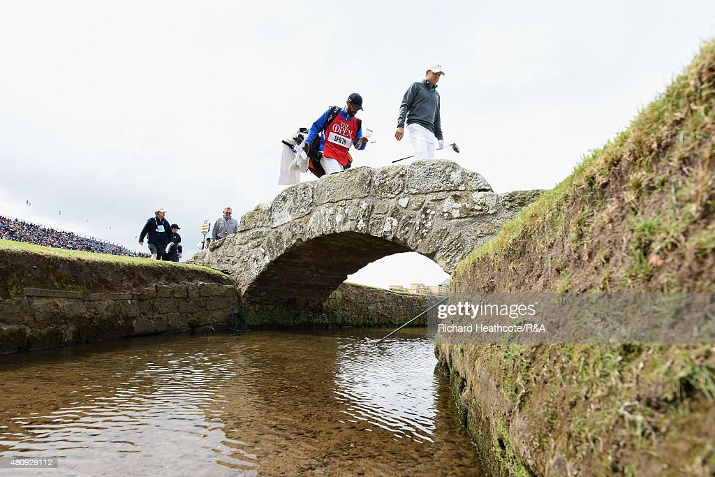 Jordan Spieth of the USA and his caddy Michael Greller walk across the Swilcan Bridge during the first round of the 144th Open Championship at The Old Course on July 16, 2015 in St Andrews, Scotland.