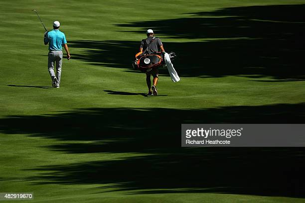 Jordan Spieth of the USA and his caddy Michael Greller walk down a fairway during a practice round for the World Golf Championship Bridgestone...