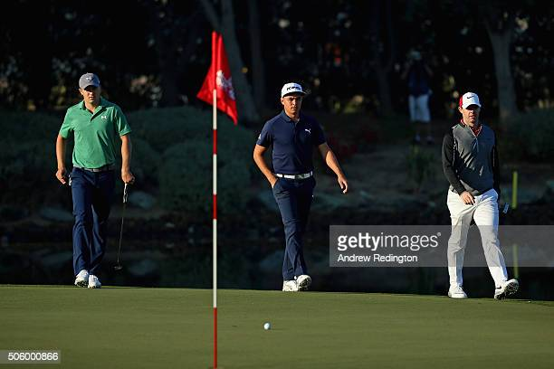 Jordan Spieth of the USA Rickie Fowler of the USA and Rory McIlroy of Northern Ireland walk onto the 12th green during the first round of the Abu...