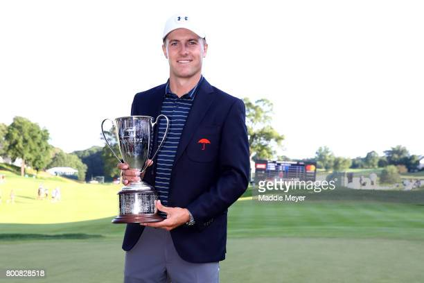Jordan Spieth poses with the winners trophy after defeating Daniel Berger in a playoff in the final round of the Travelers Championship at TPC River...