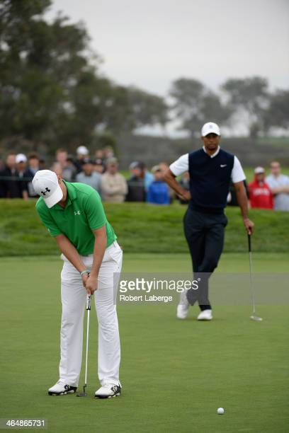 Jordan Spieth putts on the 8th green as Tiger Woods looks on during the second round of the Farmers Insurance Open on Torrey Pines South on January...