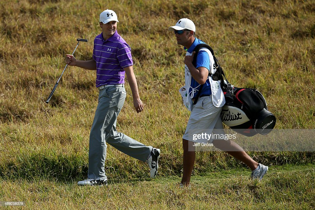 Jordan Spieth smiles with his caddie Michael Grelller in the first round of the Northern Trust Open at the Riviera Country Club on February 13, 2014 in Pacific Palisades, California.