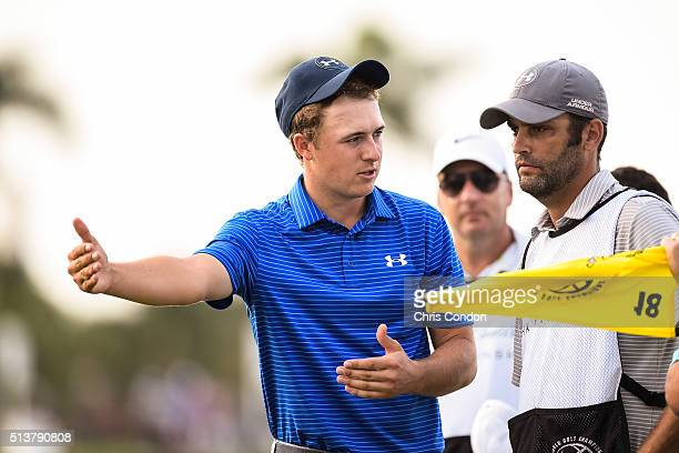 Jordan Spieth speaks with caddie Michael Greller after putting on the 18th hole green during the second round of the World Golf ChampionshipsCadillac...