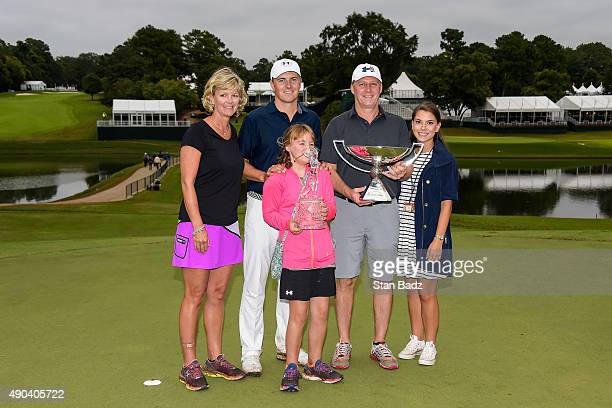 Jordan Spieth stands with members of his family and his girlfriend Annie Verret while posing with the tournament trophy and FedExCup trophy following...