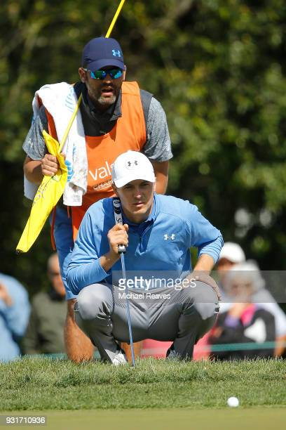 Jordan Spieth talks with his caddie as they look over a putt on the seventh green during the first round of the Valspar Championship at Innisbrook...