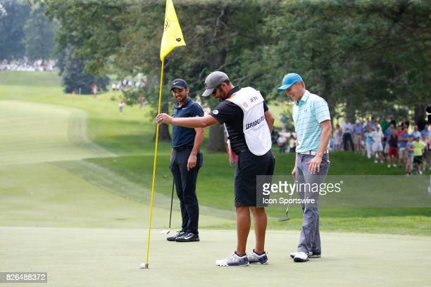 Jordan Spieth's caddie Michael Greller gently removes the flag stick as the ball hangs on the edge of the cup as Jordan Spieth and Jason Day watch on...