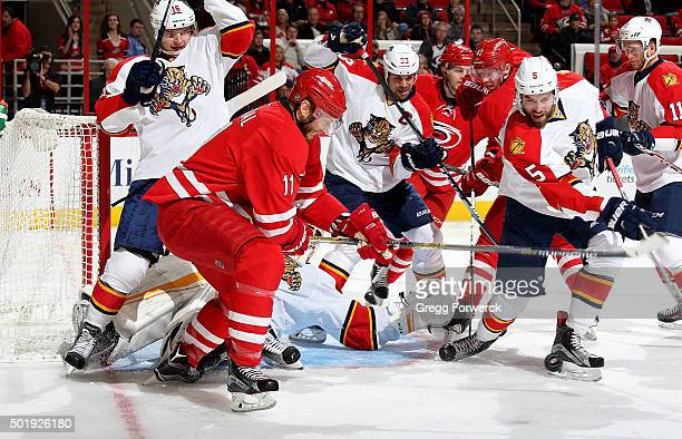 Jordan Staal of the Carolina Hurricanes and Aaron Ekblad of the Florida Panthers battle for the puck near the crease as Roberto Luongo goes down to...