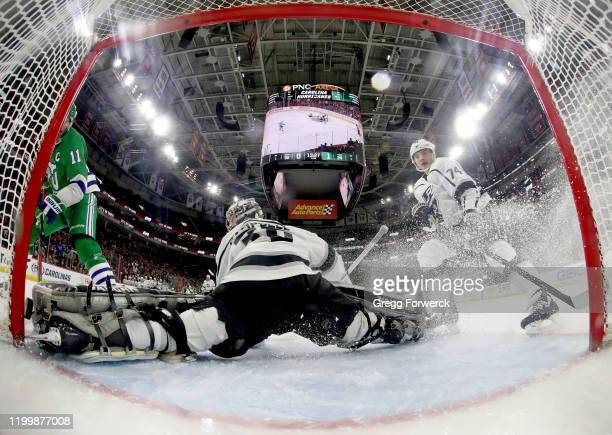 Jordan Staal of the Carolina Hurricanes attempts to backhand the puck between the pipe and the skate of Jack Campbell of the Los Angeles Kings who...