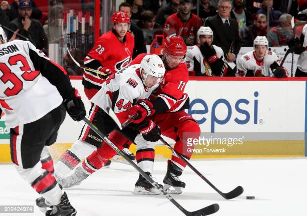 Jordan Staal of the Carolina Hurricanes battles for a loose puck with JeanGabriel Pageau of the Ottawa Senators during an NHL game on January 30 2018...