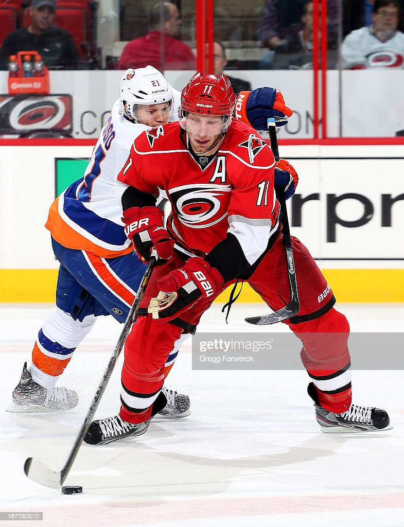 Jordan Staal #11 of the Carolina Hurricanes defends the puck while being stick checked by Kyle Okposo #21 of the New York Islanders during their NHL game at PNC Arena on April 23, 2013 in Raleigh, North Carolina.