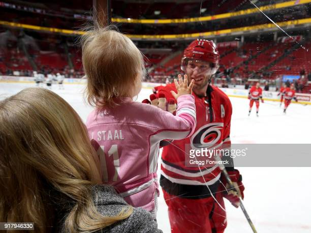 Jordan Staal of the Carolina Hurricanes greets his daughter at the glass during warmups prior to an NHL game against the Los Angeles Kings on...