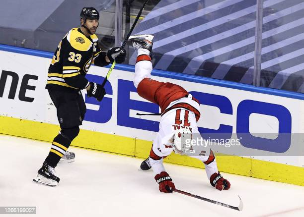 Jordan Staal of the Carolina Hurricanes is checked by Zdeno Chara of the Boston Bruins during the third period in Game Two of the Eastern Conference...