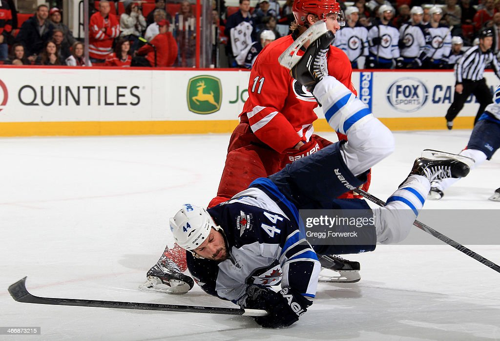 Jordan Staal #11 of the Carolina Hurricanes upends Zach Bogosian #44 of the Winnipeg Jets during an NHL game at PNC Arena on February 4, 2014 in Raleigh, North Carolina.